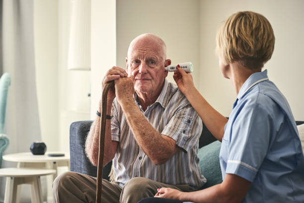 Healthcare worker checking senior man's temperature while sitting on sofa at care home