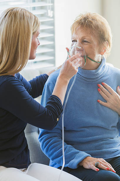 nurse is helping put an oxygen mask