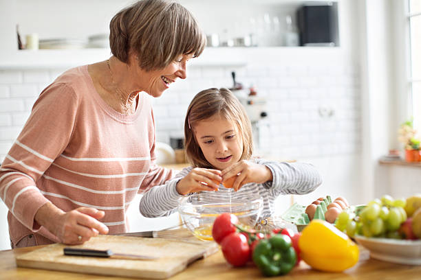Happy grandmother teaching little girl how to cook eggs