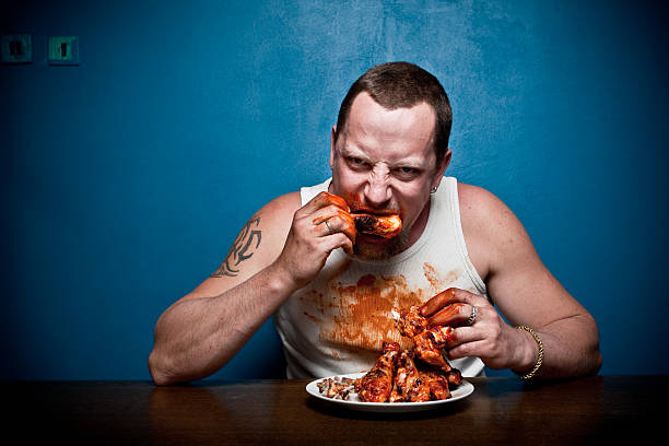 Big hungry muscular man eating meat - grilled chicken