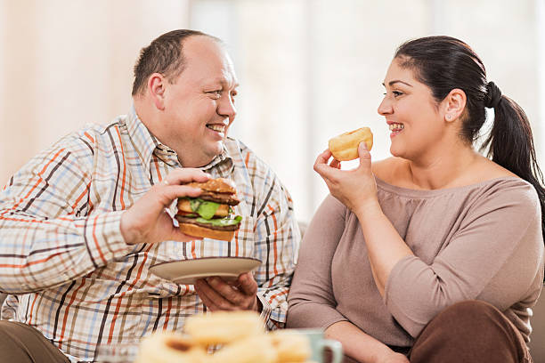 Happy overweight mid adult couple looking at each other and talking while eating unhealthy food together.