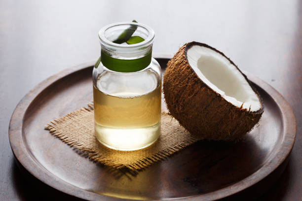 Coconut oil with fresh coconut half on wooden background
